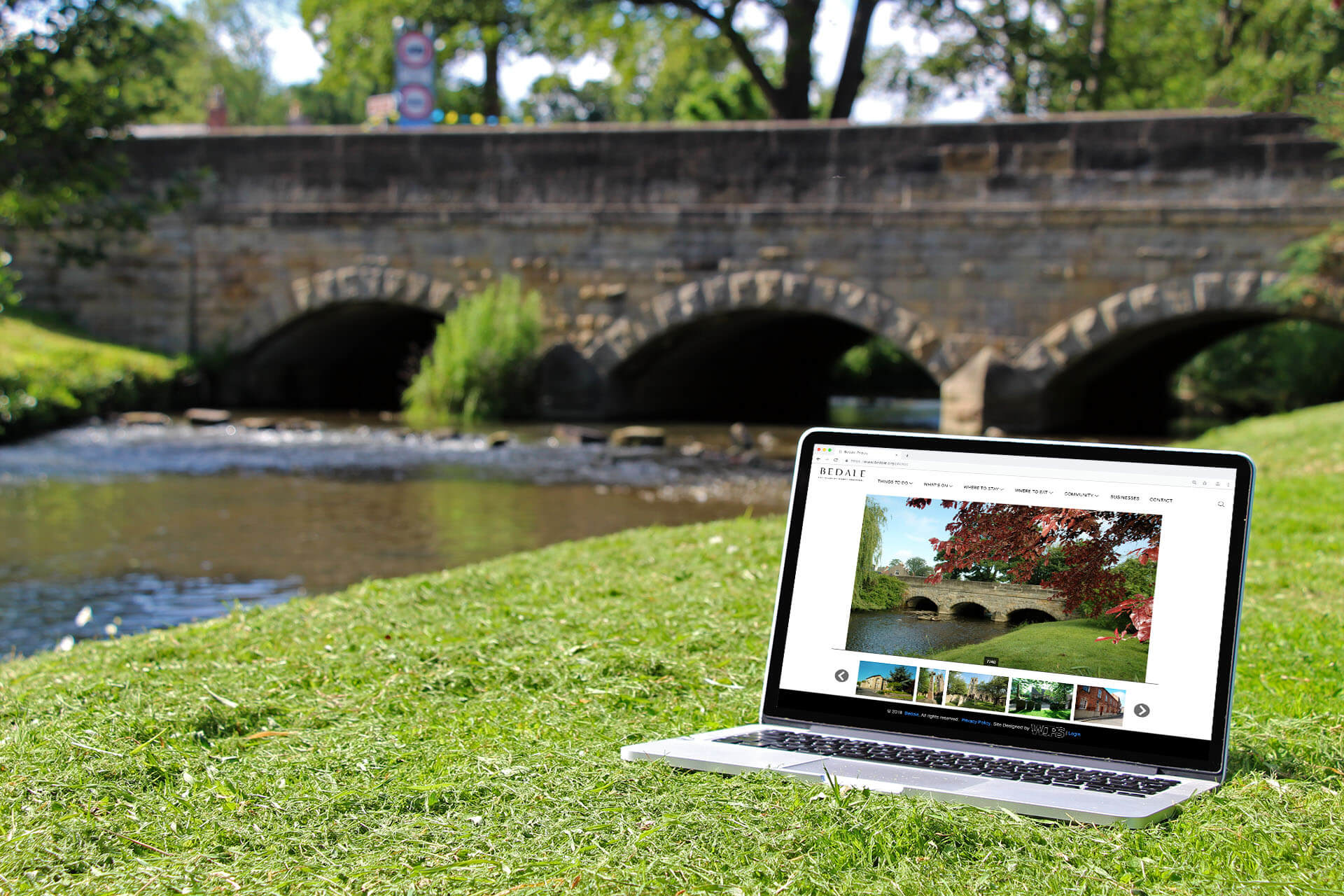 Macbook overlooking stone bridge displaying the image of the location it is at