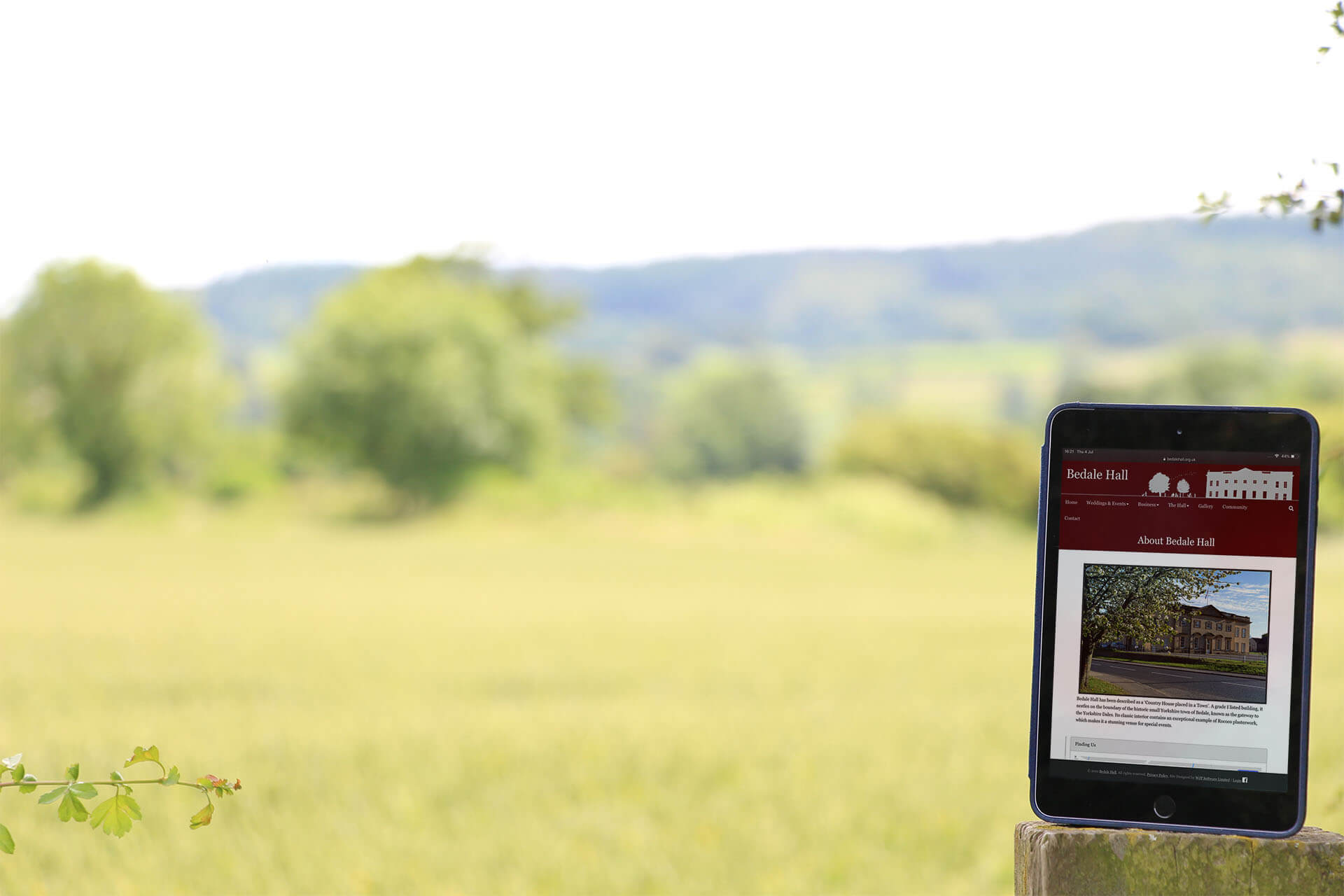 iPad standing on wooden post overlooking a field